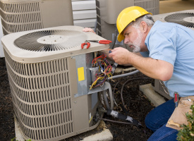 heating & cooling technician servicing air conditioner